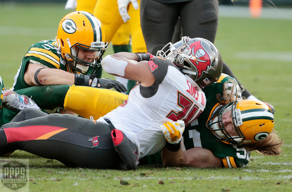 Green Bay Packers inside linebacker Blake Martinez (50) and  outside linebacker Clay Matthews (52) tackle Tampa Bay Buccaneers running back Charles Sims (34) after a 8-yard gain late in the 4th quarter. <br /> The Green Bay Packers hosted the Tampa Bay Buccaneers at Lambeau Field in Green Bay,  Sunday, Dec. 3, 2017. The Packers won in 26-20 in Overtime.   STEVE APPS FOR THE STATE JOURNAL.