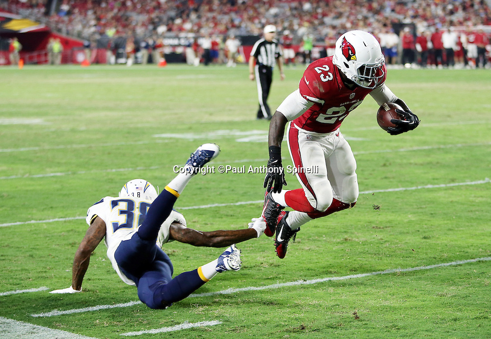 Arizona Cardinals running back Marion Grice (23) gets tripped up by San Diego Chargers cornerback Manny Asprilla (38) as he catches a pass that gives the Cardinals third down and 1 yard to go at the Chargers 2 yard line during the 2015 NFL preseason football game against the San Diego Chargers on Saturday, Aug. 22, 2015 in Glendale, Ariz. The Chargers won the game 22-19. (©Paul Anthony Spinelli)