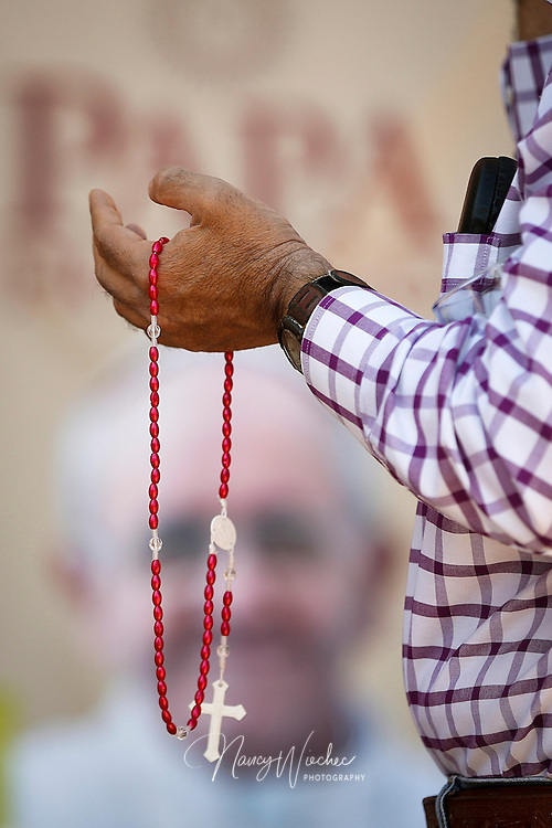 A man holds a rosary as people pray for the intentions of Pope Francis outside Sacred Heart Parish in the Secundo Barrio of El Paso, Texas, Feb. 15. During the pope's visit to Mexico, members of Sacred Heart prayed twice each day for his intentions of mercy and peace and for his safety. The church is located a few blocks from the border with Mexico. (CNS photo/Nancy Wiechec)