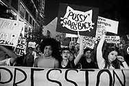 "After a presidential campaign stained by sexist comments, feminist protesters gather against President-elect Donald Trump in downtown Miami on November 11, 2016 holding a sign with the slogan ""pussy grabs back."" (photo by Samuel Navarro)"