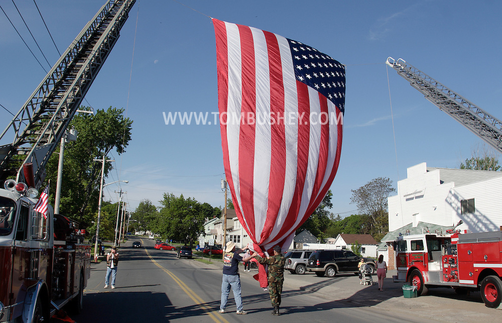 Middletown, NY - A large American flag is raised between two ladder trucks before the start of Middletown-Wallkill Veterans Council Memorial Day ceremonies and parade on May 26, 2008.