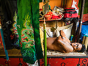 04 FEBRUARY 2017 - BANGKOK, THAILAND:  An opera performer rests on top of a crate of props and costumes before a Chinese opera at the Phek Leng Keng Shrine in the Khlong Toey section of Bangkok. Many Chinese shrines and temples host Chinese operas during the Lunar New Year. Lunar New Year was January 28 this year and opera troupes are finishing their holiday engagements at the local temples.     PHOTO BY JACK KURTZ