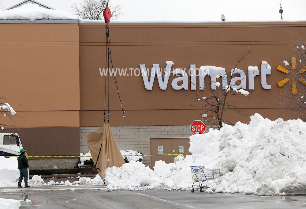 Harriman, New York - A worker, at left, watches as a crane dumps a tarp full of snow from the roof of the Walmart store to the parking lot after than 30 inches of snow fell after a storm on Feb. 27, 2010. The store remained closed until the snow was removed and the roof was inspected.