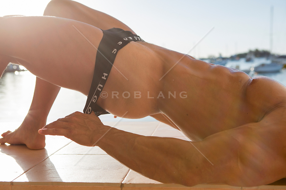 man at sunrise pulling off his underwear outdoors