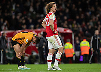 Football - 2019 / 2020 Premier League - Arsenal vs. Wolverhampton Wanderers<br /> <br /> David Luiz (Arsenal FC) looks up to the away fans and scoreboard whilst a an exhausted Diogo Jota (Wolverhampton Wanderers) bends to recover at The Emirates Stadium.<br /> <br /> COLORSPORT/DANIEL BEARHAM