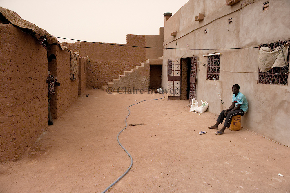 African migrant alone, sitting in a ghetto in Agadez