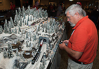 Peter Higgins of Taunton, MA maneuvers his transfer train through a mountain tunnel during a blizzard scene built by John Flanders of Clinton, MA.  The New England Region Model Railroad Convention through Sunday at the Margate Resort.  (Karen Bobotas/for the Laconia Daily Sun)