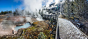 Geothermal steam surrounds a snowy boardwalk along Artists' Paint Pots Trail in Yellowstone National Park, Wyoming, USA. This image was stitched from multiple overlapping photos.