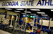 "Georgia State University's Freshman Mark Hogan is the first, and only so far, football recruit to enroll in school history at Georgia State University. He lifts weights as Head Strength and Coordination Coach Ken Coggins (left) trains with him at the school in Atlanta, Georgia April 2, 2009. He works out with the coach one-on-one four days a week. He is excited to have teammates, he said. ""It gets pretty lonely sometimes."" KENDRICK BRINSON"