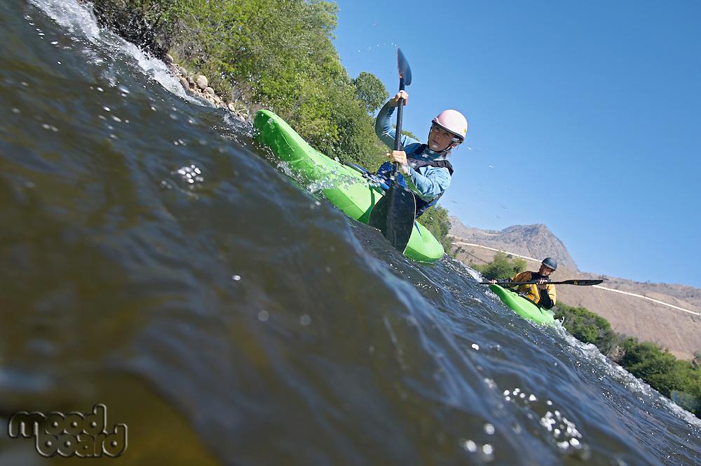 Two people kayaking in mountain river
