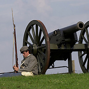 Travis Casto, 15, from Henry County, Kentucky, rests on a replica cannon  during his sentry duties as reenactors arrive Thursday for the weekend-long  Battle of Perryville, a national Civil War Reenactment, in Perryville, Ky.,  on 10/3/02. Casto was portraying a Confederate soldier with the 5th Kentucky  Infantry.  He said he didn't sleep well the night before because of the  constant howling of nearby coyotes and the sound of the ghosts of civil war  soldiers running through their camp.