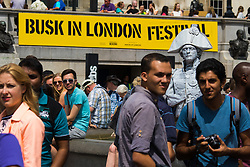 London, July 18th 2015.  A living statue rises above the crowd in Trafalgar Square as part of the Busk in London Festival aimed at showcasing the outstanding talents of many of the capital's finest street performers, including, musicians, magicians, living statues and bands.