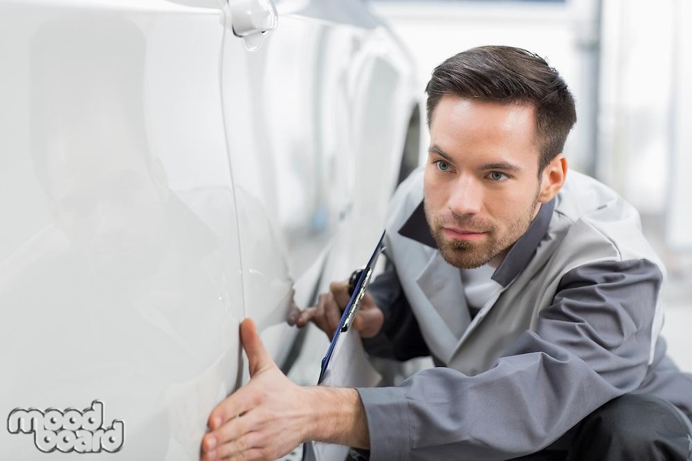 Young automobile mechanic examining car in repair store