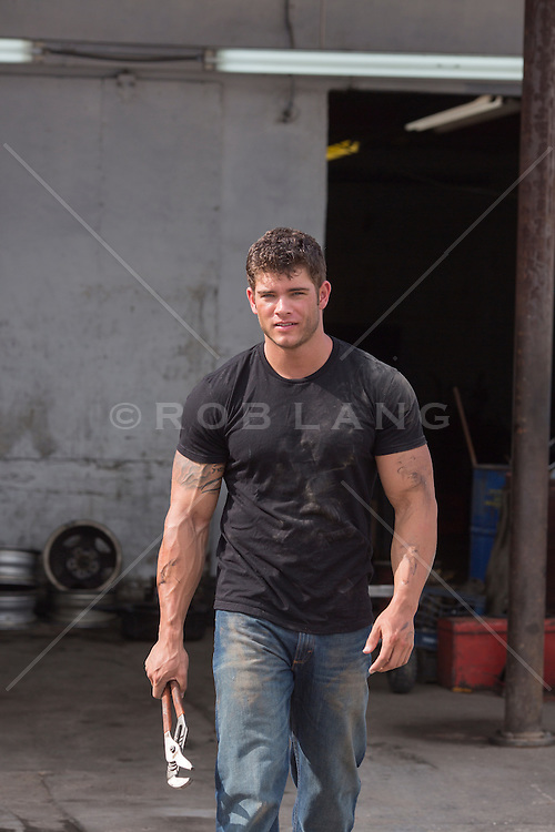 sexy auto mechanic with dirt on his tee shirt and face walking towards camera carrying a wrench
