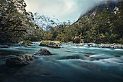 The dramatic Hollyford River at dusk clashing against the snow-capped alpine peak of Fiordland National Park, New Zealand.