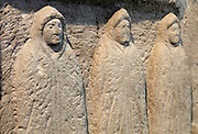 Roman carved stone depicting the genii cucullati, 3 spirits wearing hooded cloaks, commonly worshipped across Northern Europe, possibly in connection with fertility, found in the alcove of a small family shrine in the vicus, the civilian settlement outside of the fort, at the Housesteads Roman Fort Museum, Hadrian's Wall, Northumberland, England. Hadrian's Wall was built 73 miles across Britannia, now England, 122-128 AD, under the reign of Emperor Hadrian, ruled 117-138, to mark the Northern extent of the Roman Empire and guard against barbarian attacks from the Picts to the North. The Housesteads Roman Fort Museum is run by English Heritage and forms part of the Hadrian's Wall UNESCO World Heritage Site. Picture by Manuel Cohen