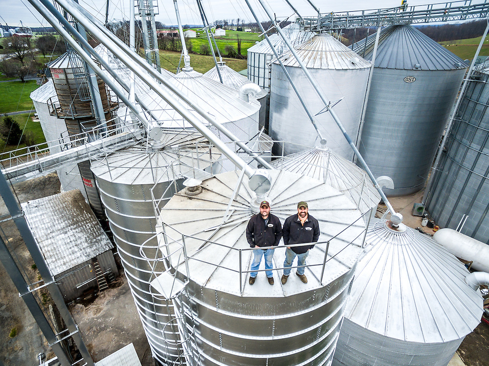Aerial view of two farmers standing on top of a silo on a farm in Harford County, Maryland.