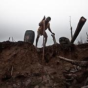 Brasile, Amazzonia, garimpo de Juma. Le miniere a cielo aperto del garimpo de Juma, dove la vita dei minatori scorre tra pericolo per un lavoro al limite e deforestazione incontrollata. Aspettando di trovare l'oro che cambi la loro vita. In questa foto un minatore scende a fatica aiutandosi con un lungo bastone. Brazil, Amazonia, garimpo de Juma. The open pit mines of garimpo de Juma, where the miners work flows between danger and uncontrolled deforestation. Waiting to find the gold that changes their lives. In this picture a miner down to fatigue with the help of a long stick.