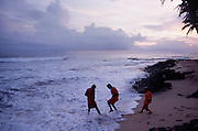 Novice monks play dodging the waves on a beach near Weligama in southern Sri Lanka.