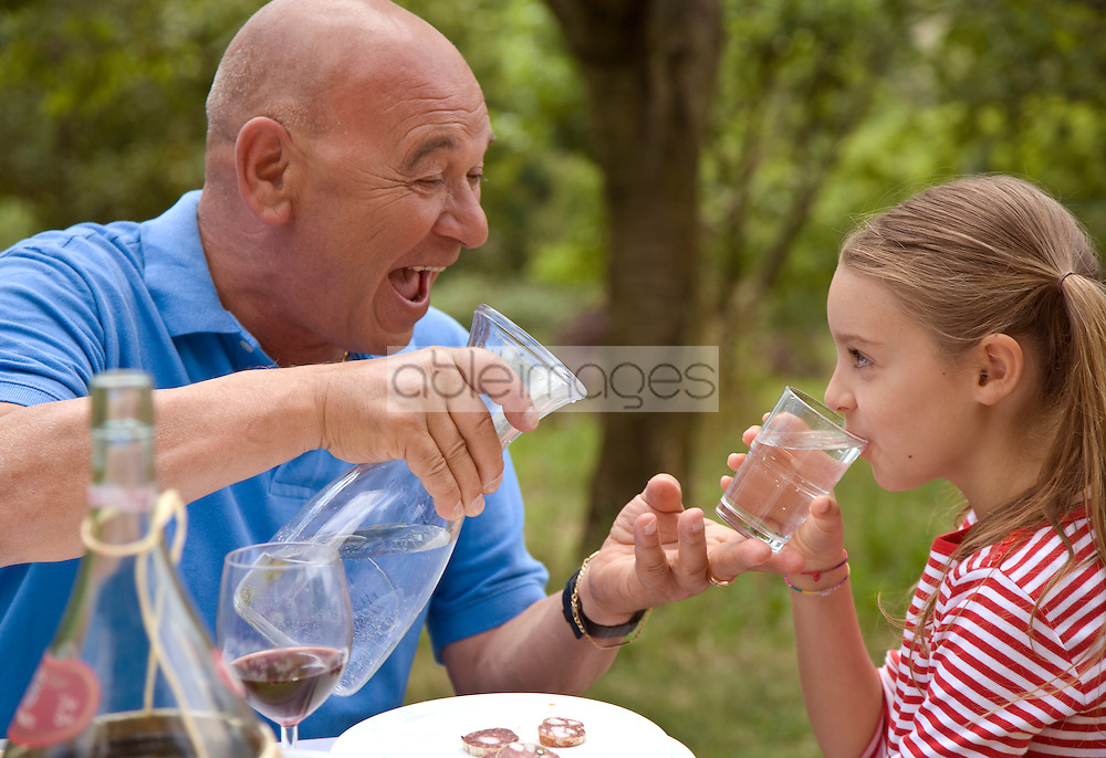 Close up of laughing grandad and granddaughter drinking water