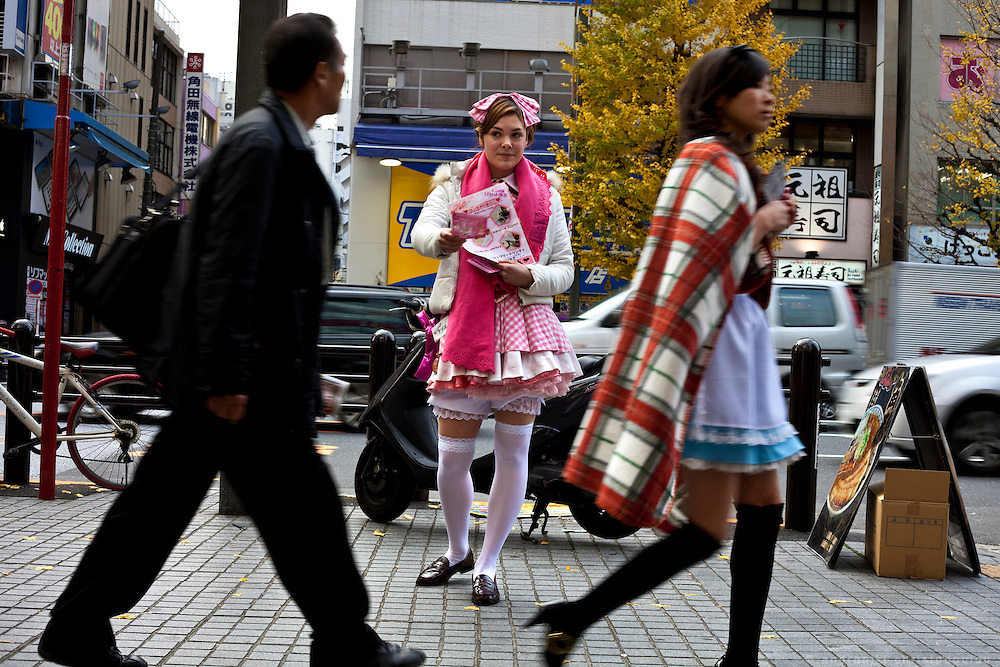 Western girl dressed as a maid, distributing leaflets that advertize a maid-cafe to passers-by in Akihabara area of Tokyo.