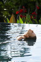 Young woman leaning backwards in natural swimming pool portrait