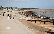 Wooden groynes, concrete steps and sea wall. Coastal defences, Felixstowe, Suffolk, England. The groynes are designed to trap beach sediment being transported down the coast by longshore drift.