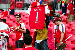 An Arsenal fan holds up a shirt showing support for embattled Manager Arsene Wenger after Arsenal win the match 2-0 to become FA Cup Winners - Rogan Thomson/JMP - 27/05/2017 - FOOTBALL - Wembley Stadium - London, England - Arsenal v Chelsea - FA Cup Final.