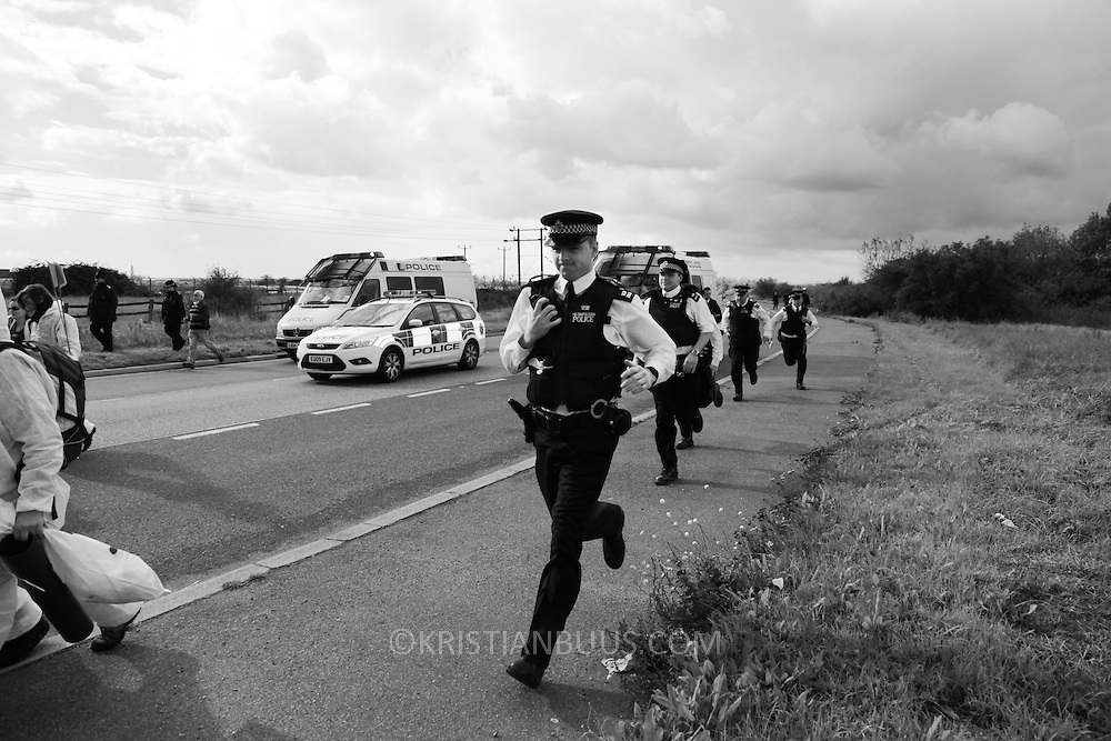 Police are stuck in their vehicles behind the human chain of activists and have to make their way pass to get ahead of the them on foot. They are now on the road heading to the refinery and the blockade held by a group of women locked onto two vans. ..Crude Oil Awakening is a coalition of climate change activist groups. On Saturday Oct 16 they shut the only entrance to Coryton oil refinery in Essex, UK with the aim of highlighting the issues of climate change and the burning of fossil fuels. The blockade meant that a great number of trucks with oil were not able to leave the refinary during the day of action.