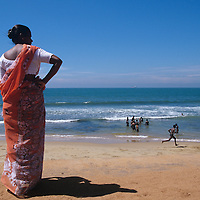 Sri Lanka, Woman walks on beach along beach by Galle Face Green