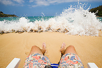 A first person view of sitting in a chair on the beach looking out at Moloa'a bay on Northeast Kauai, Hawaii, USA.