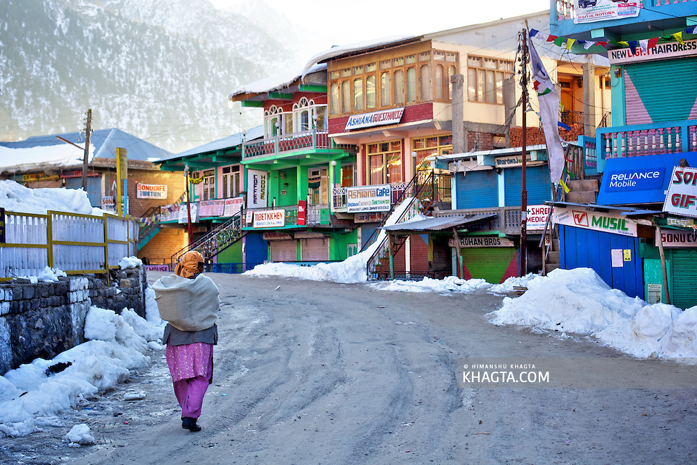 A lady walks on the slippery road outside Sangla Market in a sunny winter Morning