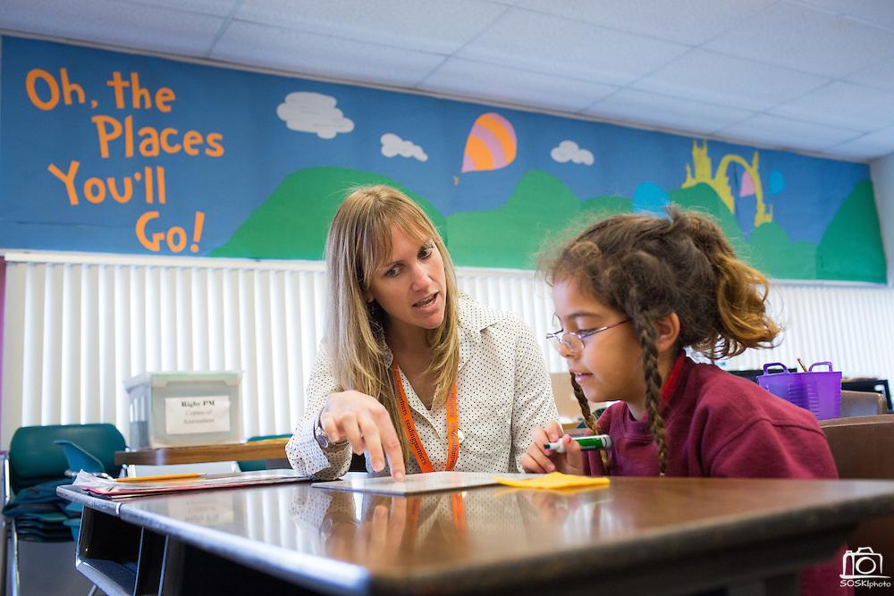 Reading Partners Regional Site Coordinator Claire Bleymaier of San Jose tutors third grader Isabella Ruiz, 8, during the Reading Partners tutoring program at Rose Elementary School in Milpitas, California, on December 8, 2014. (Stan Olszewski/SOSKIphoto)