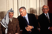 Israeli Prime Minister Benjamin Netanyahu talks with PLO leader Yasser Arafat as King Hussein of Jordan look on at a White House news conference October 2, 1996 In Washington, DC.