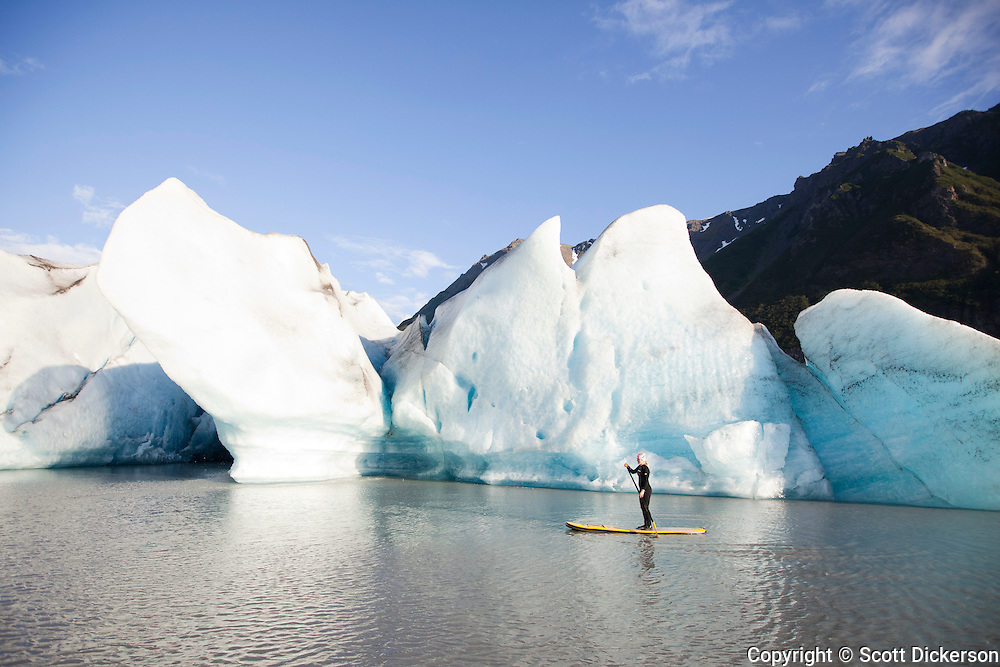 Erika Klaar stand up paddling an inflatable boardworks SHUBU SUP near the face of Grewingk Glacier. This glacier lake is accessed by a seaplane flight from Homer, Alaska. The inflatable stand up paddleboards make it possible to easily fit five paddlers adn their gear all into a small bushplane.