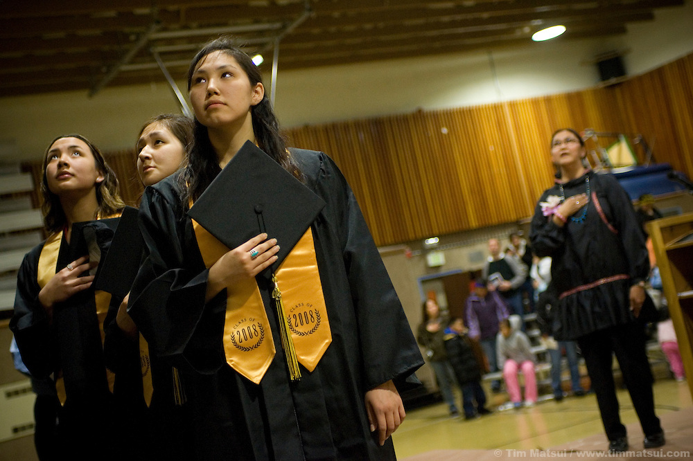 May 2, 2008 -- Kivalina, AK, U.S.A..High school graduates, from left to right, Sonja Barger, Loni Frankson, and Kandes Sage stand during the national anthem with principal Pauline Harvey in the native village of Kivalina, Alaska. Kivalina is suing 20 oil companies for property damage related to global warming; the ocean pack ice forms later and melts earlier, leaving the town vulnerable to erosive winter storms and endangering their traditional subsistence lifestyle. (Photo by Tim Matsui)