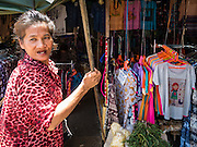 27 SEPTEMBER 2016 - BANGKOK, THAILAND:  A woman who works in the market in the Samut Songkhram train station watches a train come into the station. The train from Baen Laem to Samut Songkhram (Mae Khlong) recently resumed service. The 33 kilometer track was closed for repair for almost a year. In Samut Songkhram, the train passes over the market. Vendors pull their stands out of the way and people step out of the way as the train passes through the market. It is one of the most famous train stations in Thailand and has become an important tourist attraction in the community.    PHOTO BY JACK KURTZ