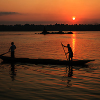 Two men paddle their pirogue down the Congo River at sunset, Kinshasha, Democratic Republic of Congo, 2011