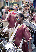 African boy with painted face lost in music drumming in the school band on parade at the Cowley Road Carnival, Oxford, England