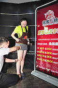 JINAN, CHINA - MAY 17: (CHINA OUT) <br /> <br /> Restaurant Offers Big Discount For Beauties wearing shortest skirt<br /> <br /> A worker measures a girl\'s exposed thigh at a hot pot restaurant on May 17, 2015 in Jinan, Shandong Province of China. There is a special price for beauties who wear short skirts, the minimum discount is 20 percent off for 8 centimeters exposed thigh, and the maximum discount is 90 percent off for 33 centimeters exposed thigh<br /> ©Exclusivepix Media