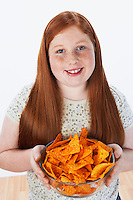 Overweight girl (13-15) holding bowl of snacks portrait