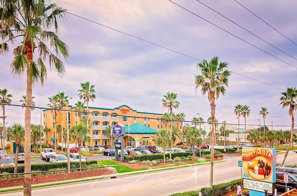 Florida state road A1A, looking southwest, is pictured from the balcony of Sunset Grille, March 19, 2016, in St. Augustine, Florida. The restaurant opened in 1990 and offers a laidback, Key West atmosphere. Signs throughout the building refer to Florida state road A1A, where the restaurant is located. The road runs along the Atlantic Ocean, from Key West to Fernandina Beach, Florida. The historic highway, which is more than 338 miles long, is a designated National Scenic Byway and holds an important place in Florida beach culture. Sunset Grille has popularized the name by using #SomewhereOnA1A, #A1ALife, and #HaveAnA1ADay on social media. In the background is Hampton Inn. (Photo by Carmen K. Sisson/Cloudybright)