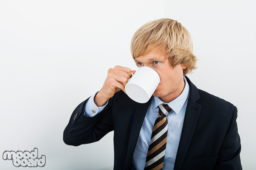 Mid adult businessman drinking coffee over white background