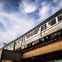 "Photo of Chicago ""L"" elevated train with a blue sky and swirly clouds."