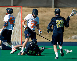 Virginia defenseman Matt Kelly (33) stands over Navy defenseman Zack Schroeder (51) after a hard hit that sent Schroeder to the turf.  The Virginia Cavaliers scrimmaged the Navy Midshipmen in lacrosse at the University Hall Turf Field  in Charlottesville, VA on February 2, 2008.