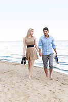Full length of young couple holding hands and walking on beach