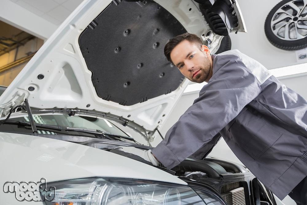 Portrait of confident male repair worker repairing car engine in repair shop