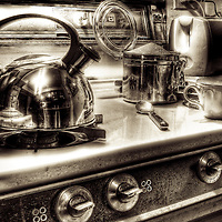 A chrome kettle ona cooker hob with coffee cup and sugar container