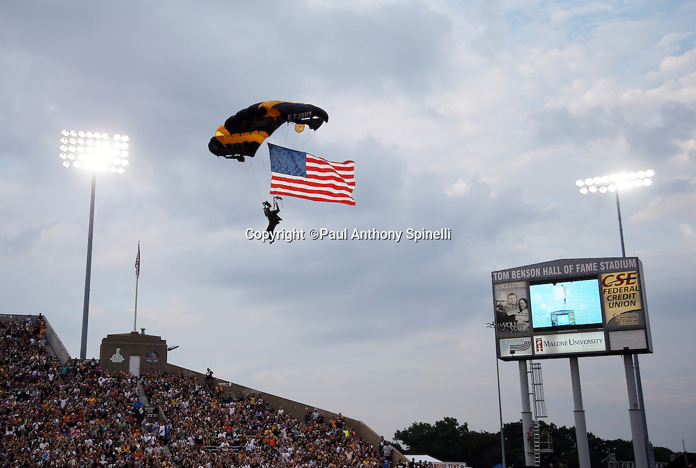 A member of the U.S. Army Golden Knights Parachute Team parachutes into the stadium with a giant United States flag flying behind him in this general view photograph of Tom Benson Hall of Fame Stadium before the Pittsburgh Steelers 2015 NFL Pro Football Hall of Fame preseason football game against the Minnesota Vikings on Sunday, Aug. 9, 2015 in Canton, Ohio. The Vikings won the game 14-3. (©Paul Anthony Spinelli)