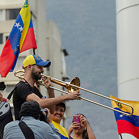 Un joven canta el himno nacional venezolano con una trompeta en un mitin en protesta por el apagón eléctrico que afecta al país. A young man sings the Venezuelan national anthem in a trumpet at a rally protesting the mega-electric blackout affecting the country.